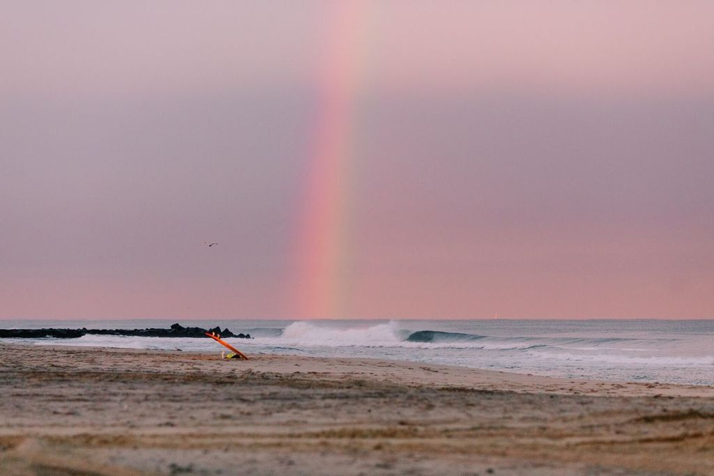 tabla de surf en la playa bajo el arco iris