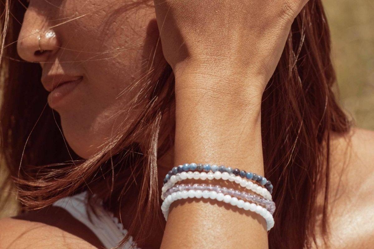 Mujer vistiendo pulseras de piedras preciosas de Piscis