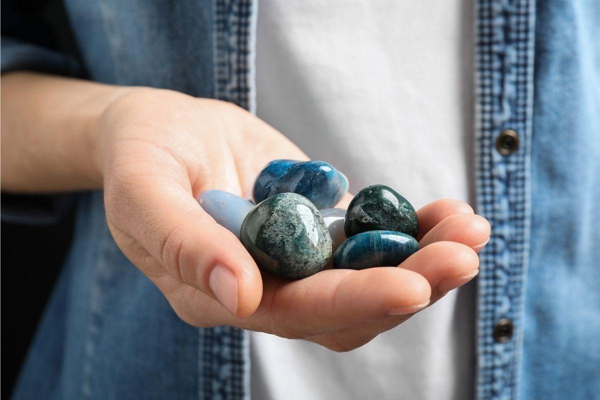 Mujer sosteniendo diferentes piedras, incluida la piedra de sangre