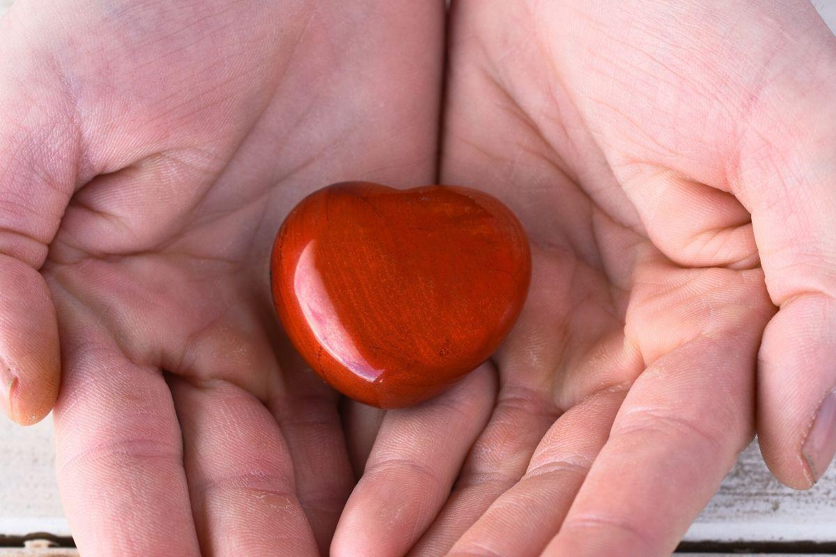 mano sosteniendo piedra de jaspe rojo