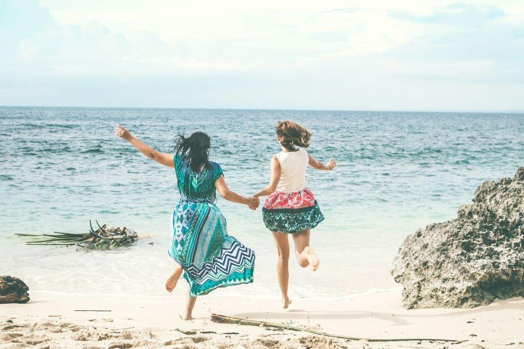 mujeres cogidas de la mano y corriendo hacia el mar