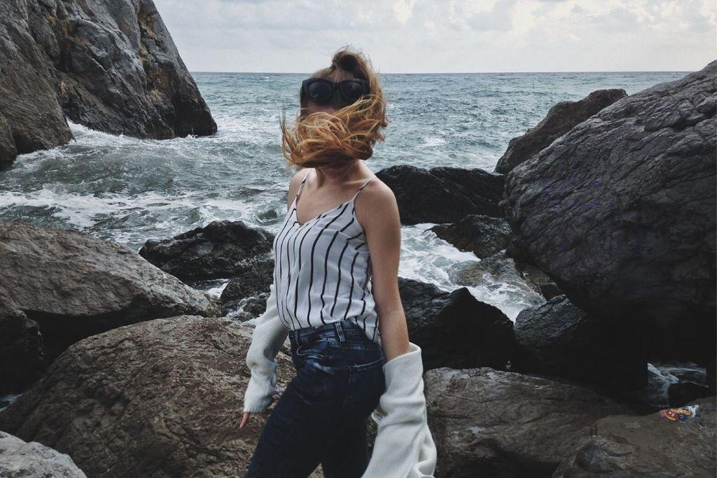 Mujer de pie frente al mar con cabello soplado